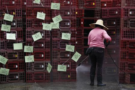 A worker cleans empty cages, which were used to transport chickens, after morning trading at a wholesale poultry market in Hong Kong April 8, 2013. REUTERS/Bobby Yip