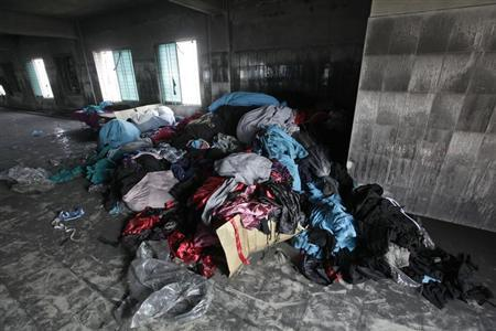Piles of clothes are seen alongside sewing machines in the Tazreen Fashions garment factory, where 112 workers died in a devastating fire last month, in Savar November 30, 2012. REUTERS/Andrew Biraj/Files