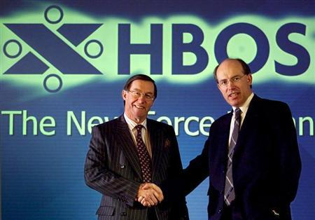 Chief executive of the Bank of Scotland Peter Burt (L) and Chief executive of the Halifax James Crosby (R) shake hands in front of the new company logo after announcing the proposed merger to create HBOS in this May 4, 2001 file photo. JE/PS/WS