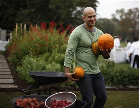 White House Chef Sam Kass drops freshly harvested pumpkins into a wheelbarrow during the fall harvest of the White House Kitchen Garden at the White House in Washington, October 20, 2010. REUTERS/Jason Reed