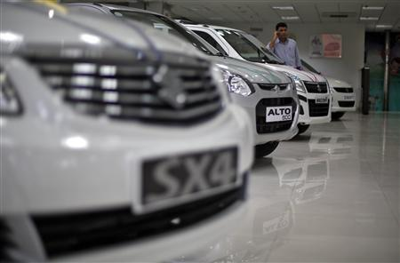 A sales executive speaks on his mobile phone as he stands in between Maruti Suzuki cars inside a showroom in New Delhi April 9, 2013. India's annual car sales fell for the first time in a decade in the financial year just ended, official data showed on Wednesday, calling into question bullish growth expectations that fuelled billion-dollar bets from global manufacturers. Picture taken April 9, 2013. REUTERS/Adnan Abidi