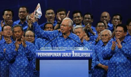 Malaysia's Prime Minister Najib Razak (C) holds his National Front coalition's manifesto during its launch ahead of the elections in Kuala Lumpur April 6, 2013. REUTERS/Bazuki Muhammad