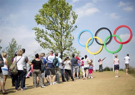 People queue to have their pictures taken with the Olympic Rings in the Olympic Park during the London 2012 Olympic Games August 11, 2012. REUTERS/Neil Hall/Files