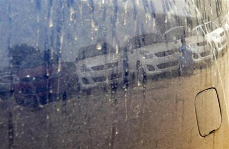 An employee is reflected on the body of a Maruti Suzuki car as he cleans dust from the other cars at a Maruti Suzuki stockyard on the outskirts of Ahmedabad April 10, 2013. REUTERS/Amit Dave