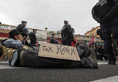 French gendarmes stand near an anti G20 demonstrator who takes part in protest against globalisation and tax havens at the French-Monaco border in Cap d'Ail, southeastern France, November 3, 2011. REUTERS/Eric Gaillard