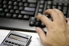 Работник банка Multiva Bank в Мехико делает подсчеты при помощи калькулятора, 9 августа 2011 года. Совет директоров российского монополиста в производстве калийных удобрений Уралкалия рекомендовал по итогам прошлого года дополнительные дивиденды в размере 3,9 рубля на акцию и одобрил выпуск дебютных евробондов на сумму до $700 миллионов сроком до 7 лет. REUTERS/Carlos Jasso