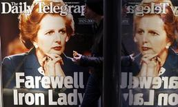 A man walks in front of a newspaper advertisement with the portrait of former British prime minister Margaret Thatcher in Sydney April 9, 2013. REUTERS/Daniel Munoz