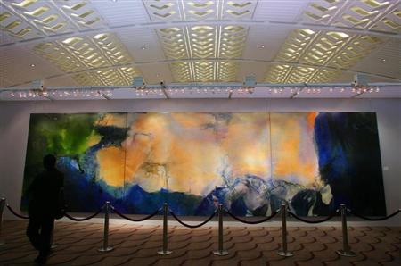 A visitor looks at a 2.8-metre by 10-metre triptych by Chinese painter Zao at Christie's auction house in Hong Kong. REUTERS/Bobby Yip