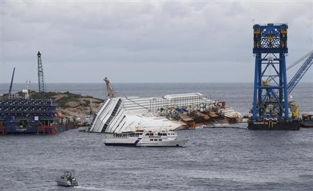 Relatives of victims stand on a ferry in front of the capsized cruise liner Costa Concordia outside Giglio harbour January 13, 2013. REUTERS/Stefano Rellandini