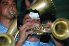 Музыкант с банкнотой достоинством 20 динаров играет на трубе в Гуче, Сербия, 22 августа 1999 года. Сербия зовет к себе российские госбанки, сообщил сербский премьер Ивица Дачич в Москве. REUTERS/Reuters Photographer