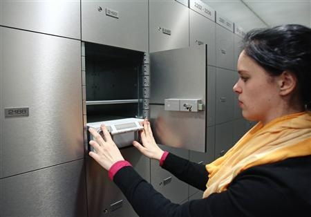 A woman pushes a deposit box into a compartment in the safe room of an Austrian bank in Vienna April 10, 2013. REUTERS/Heinz-Peter Bader