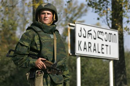 A Russian serviceman stands near a road sign as troops prepare to leave a checkpoint in the Georgian village of Karaleti, some 90 km (56 miles) west of Tbilisi October 7, 2008. REUTERS/Sergei Karpukhin (GEORGIA) - RTX9ANB