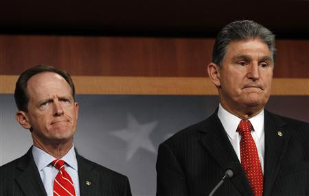 Senator Pat Toomey (R-PA) (L) and Senator Joe Manchin (D-W.VA) (R) hold a news conference on background checks for firearms on Capitol Hill in Washington April 10, 2013. REUTERS-Gary Cameron (UNITED STATES - Tags: POLITICS CRIME LAW)