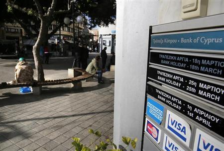 People sit near a branch of Bank of Cyprus in Nicosia March 27, 2013. REUTERS/Yannis Behrakis