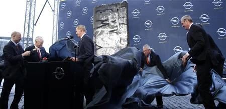 Karl Thomas Neumann (3rd L), Chief Executive of Adam Opel AG and President of General Motors Europe, Dan Akerson (2nd L), General Motors Chairman and Chief Executive Officer, and Stephen Girsky (L), General Motors Vice Chairman and Chairman of the Opel Supervisory Board unveil a part of the Berlin Wall in front of the Adam Opel AG headquarters in Ruesselsheim April 10, 2013. REUTERS/Lisi Niesner