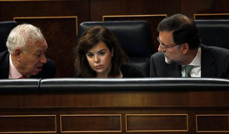Spain's Prime Minister Mariano Rajoy (R), Deputy Prime Minister Soraya Saenz de Santamaria (C) and Foreign Minister Jose Manuel Garcia Margallo react as opposition Socialist Party leader Alfredo Perez Rubalcaba (not pictured) asks about the results of the last European Council during a parliamentary session at the Spanish parliament in Madrid April 10, 2013. REUTERS/Susana Vera