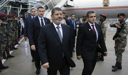 Egypt's President Mohamed Mursi (C) arrives at King Shaka Airport in the coastal city of Durban during his visit to South Africa for the 5th BRICS Summit March 27, 2013. REUTERS/Egyptian Presidency/Handout