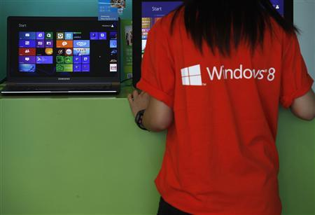 An attendant checks a computer during the launch of Microsoft Windows 8 operating system in Hong Kong in this October 26, 2012 file photo. Personal computer sales plunged 14 percent in the first three months of the year, the biggest decline in two decades of keeping records, as tablets continue to gain in popularity and buyers appear to be avoiding Microsoft Corp's new Windows 8 system, according to a leading tech tracking firm. REUTERS/Bobby Yip/Files