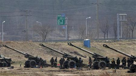 South Korean soldiers of an artillery unit take part in an artillery drill with 155mm Towed Howitzers as part of the annual joint military exercise ''Foal Eagle'' by the U.S. and South Korea, near the demilitarized zone (DMZ) which separates the two Korea, in Goseong, about 330 km (205 miles) northeast of Seoul April 9, 2013. REUTERS/Kim Hong-Ji