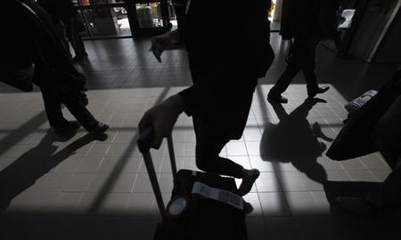 Passengers cast shadows as they walk along a terminal at Los Angeles International Airport in Los Angeles, California March 4, 2013. REUTERS/Mario Anzuoni