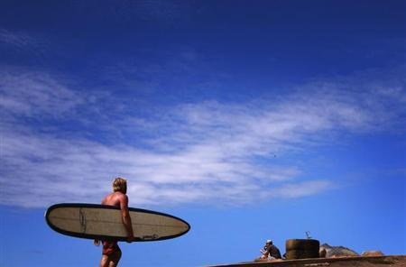A surfer carrying his board walks towards the beach along a path at Long Reef Beach on a sunny day in Sydney April 2, 2013. REUTERS/David Gray