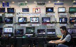 Работник компьютерного магазина сидит у полок с ноутбуками в Тайбэе 31 августа 2011 года. Продажи персональных компьютеров в первом квартале 2013 года рухнули на 14 процентов в годовом исчислении, показав максимальное сокращение за два десятилетия наблюдений, свидетельствуют данные аналитической компании IDC. REUTERS/Pichi Chuang