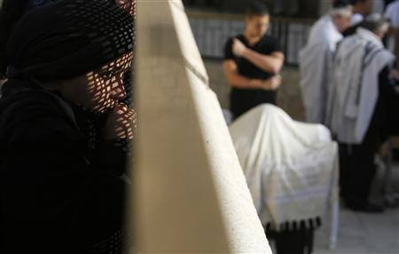 A woman looks at men praying from behind a metal screen at the Western Wall Judaism's holiest prayer site, in Jerusalem's Old City April 11, 2013. REUTERS/Baz Ratner