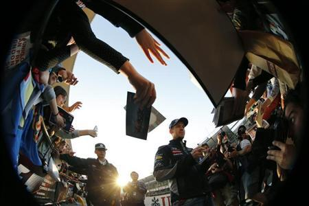 Red Bull Formula One driver Sebastian Vettel (C) of Germany signs his autograph at the Chinese Grand Prix at the Shanghai International Circuit April 11, 2013. REUTERS/Kim Kyung-Hoon