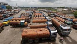 Автоцистерны для перевозки нефтепродуктов на стоянке в окрестностях Калькутты 14 августа 2012 года. Цены на нефть Brent держатся ниже $106 за баррель из-за снижения прогнозов мирового потребления и роста запасов в США. REUTERS/Rupak De Chowdhuri