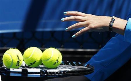 A ball girl places balls on the racket of Somdev Devvarman during his men's singles match against Jerzy Janowicz of Poland at the Australian Open tennis tournament in Melbourne, January 16, 2013. REUTERS/Tim Wimborne/Files