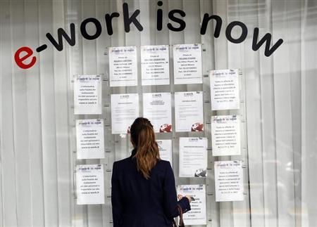 A woman checks job offers outside a recruitment agency in downtown Milan April 3, 2012. REUTERS/Alessandro Garofalo