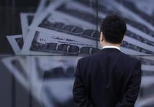 Бизнесмен смотрит на экран, изображающий стодолларовые купюры, в Токио 8 апреля 2013 года. Доллар приостановил рост к иене перед покорением рубежа 100 иен, но иена подешевела до трехлетнего минимума к евро. REUTERS/Toru Hanai