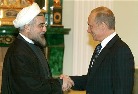 Hassan Rowhani, the head of Iran's Supreme National Security Council (L) and Russian President Vladimir Putin shake hands in Moscow, November 10, 2003. REUTERS/Pool/Mikhail Metzel