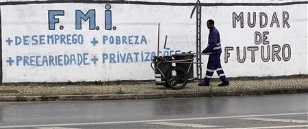 A city cleaner works near a wall with graffiti that reads ''International Monetary Fund + Unemployment + Poverty + Precariousness + Privatization'' in Bobadela April 10, 2013. REUTERS/Hugo Correia