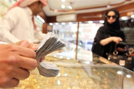 A salesman counts money as a woman walks past a jewellery shop at the gold market in Riyadh, March 11, 2013. REUTERS/Stringer/Files