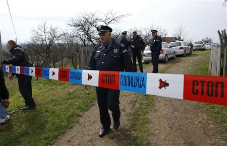 A policeman stands guard in the village of Velika Ivanca, about 40 km (25 miles) southwest of Belgrade April 9, 2013. REUTERS/Marko Djurica