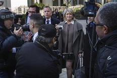 Martha Stewart (C) holds a camera as she departs the New York state Supreme Court after testifying in Manhattan March 5, 2013. REUTERS/Lucas Jackson