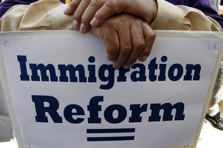 A man holds an immigration reform protest sign during a rally for immigration reform near Senator Dianne Feinstein's office, in Los Angeles, California, April 10, 2013. REUTERS/Jonathan Alcorn