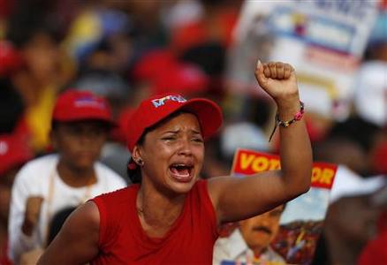 A supporter of Venezuela's acting President and presidential candidate Nicolas Maduro cries as a screen shows Venezuela's late President Hugo Chavez during Maduro's closing campaign rally in Caracas April 11, 2013. REUTERS-Tomas Bravo