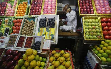 A fruit vendor speaks on his phone while sitting at his fruit stall at a wholesale market in Mumbai March 14, 2013. REUTERS/Vivek Prakash/Files