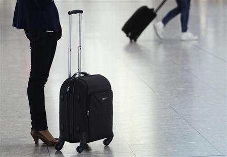 Passengers wait for flights with their luggage at Heathrow airport in London March 16, 2012. REUTERS/Luke MacGregor