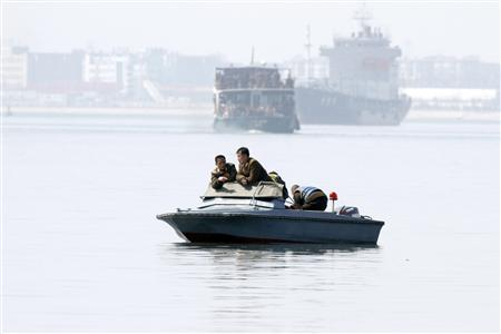 North Korea soldiers lean in a boat on Yalu River, near the North Korean town of Sinuiju, opposite the Chinese border city of Dandong, April 10, 2013. REUTERS/Jacky Chen