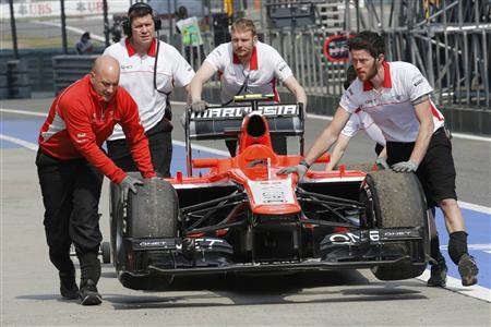 Crew members push the car of Marussia Formula One driver Max Chilton of Britain after it stalled on the track, due to technical problems, during the second practice session of the Chinese F1 Grand Prix at the Shanghai International circuit, April 12, 2013. REUTERS/Kim Kyung-Hoon