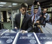 Сотрудник Сената берет стопку книг о бюджетном плане США на 2014 финансовый год в Вашингтоне, 10 апреля 2013 года. Республиканцы, демократы и даже Белый дом дистанцировались от предложения президента США Барака Обамы сократить программы социального обеспечения и пособия, в очередной раз подтвердив сложность достижения компромисса в сокращении расходов и дефицита бюджета. REUTERS/Gary Cameron