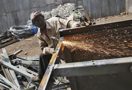 A worker welds a metal table at a scrap yard at an industrial area in Mumbai April 12, 2013. REUTERS/Vivek Prakash/Files