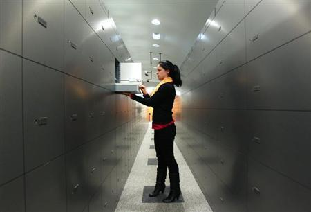 A woman takes a deposit box out of a compartment in the safe room of an Austrian bank in Vienna April 10, 2013. REUTERS/Heinz-Peter Bader