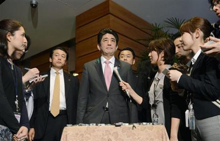 Japan's Prime Minister Shinzo Abe (C) speaks to media after a meeting with cabinet ministers at his official residence in Tokyo, in this photo taken by Kyodo April 12, 2013. REUTERS/Kyodo