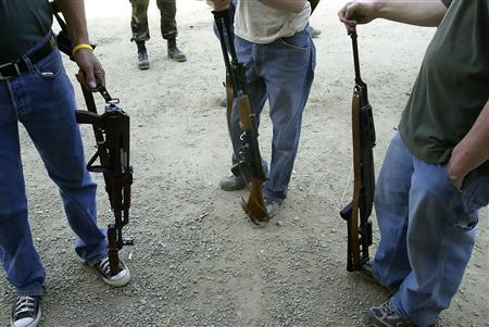 A group of men with automatic weapons for sale stand at the gun show at the Knob Creek Machine Gun Shoot near West Point, Kentucky April 9, 2005. REUTERS/Rick Wilking