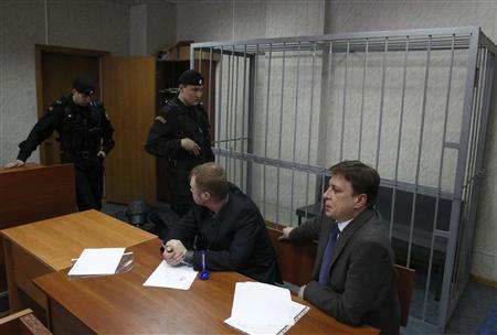 Attorneys of dead anti-corruption lawyer Sergei Magnitsky sit in front of an empty defendants cage during a court session in Moscow March 22, 2013. REUTERS/Mikhail Voskresensky