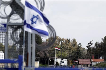 An Israeli flag (L) flutters near a Syrian flag at the Kuneitra border crossing between Israel and Syria, on the Golan Heights in this March 5, 2013 file photo. REUTERS/Baz Ratner/Files